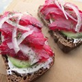 Beet and sugar–cured rockfish on fig and oat rye bread with caraway sour cream