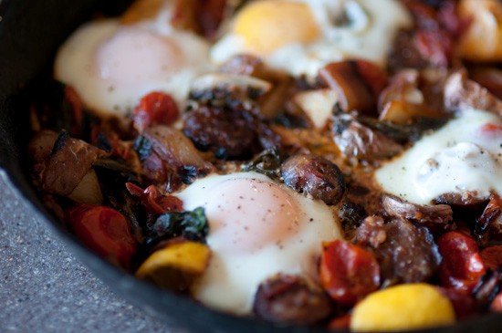 Braised sausage and tomatoes with Swiss chard and poached eggs