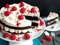 Chocolate meringue cake with whipped cream and raspberries