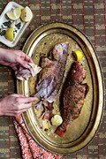 Lemon-stuffed fried fish with green chile rub (Samak imtabal maqli)